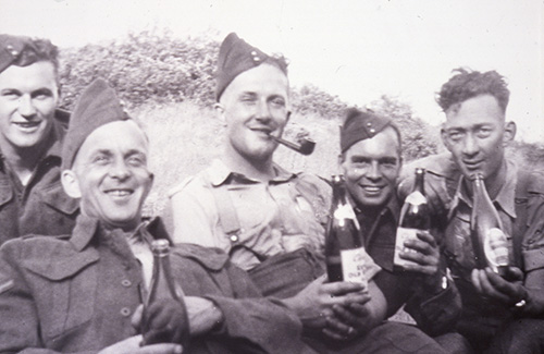 5 men in army uniforms, some holding bottles of beer, smile for the camera. Cliff is centre with a pipe in his mouth.