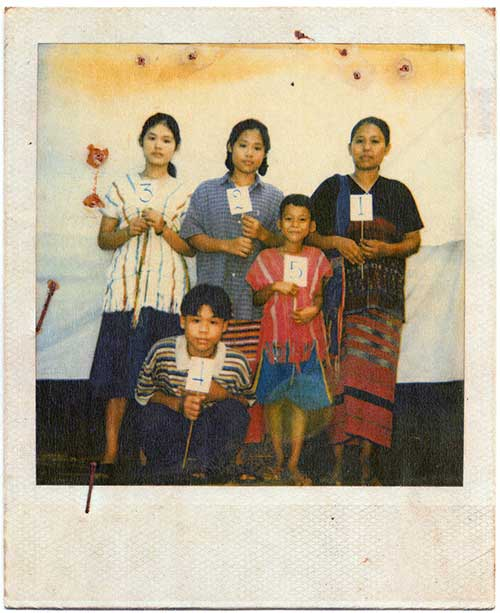 A polaroid photo of a family of 5, mother, two daughters and two sons, stand against a white tarp  backdrop each holding a small sign with a number, 1 to 5.